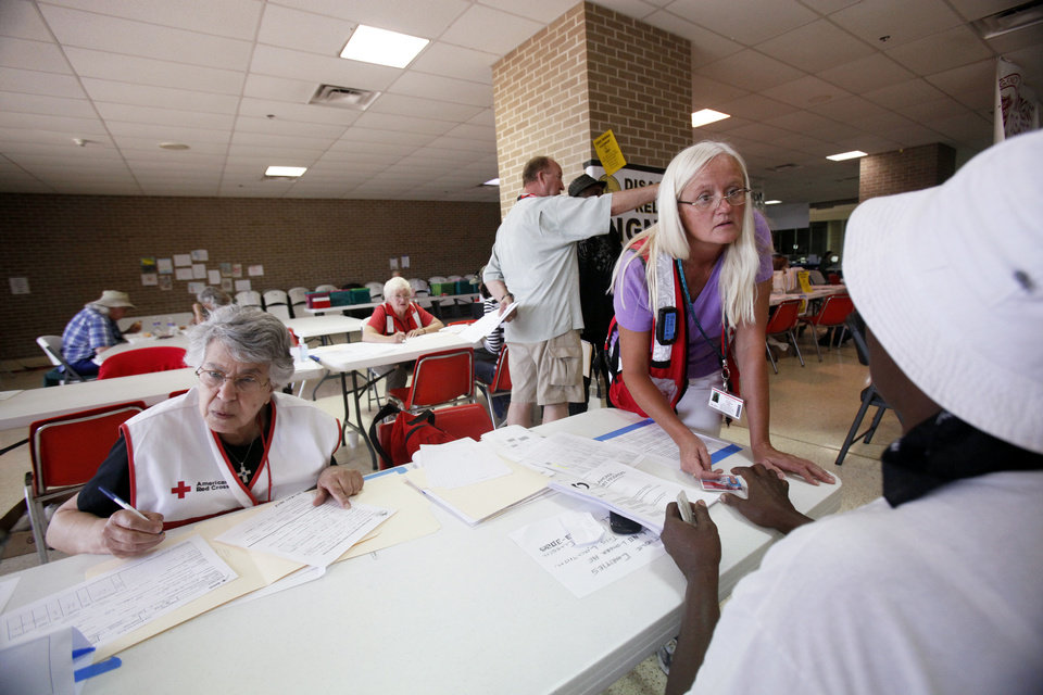 Red Cross volunteers Lily Boutros, left, of Massachusetts, and Tina Spencer, of Utah, help victims of the recent tornadoes with required relief paperwork Wednesday at Westmoore High School. Photo by Aliki Dyer, The Oklahoman. <strong>Aliki Dyer</strong>
