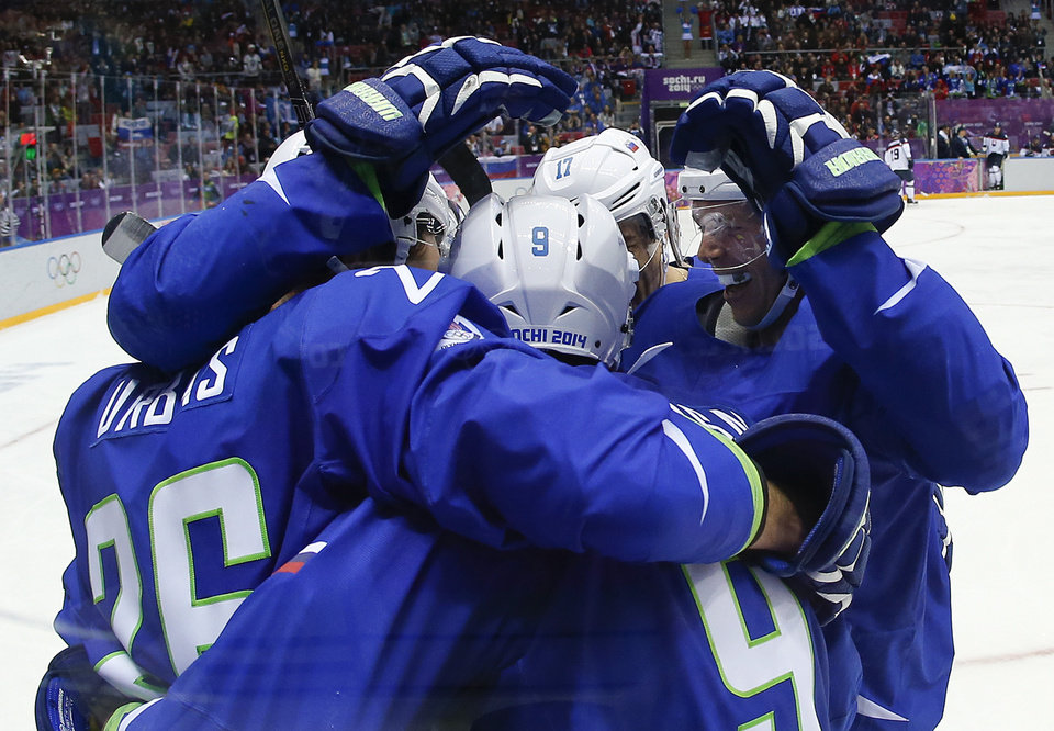 Photo - Team Slovenia celebrate a goal against Slovakia in the third period of a men's ice hockey game at the 2014 Winter Olympics, Saturday, Feb. 15, 2014, in Sochi, Russia. (AP Photo/Julio Cortez)