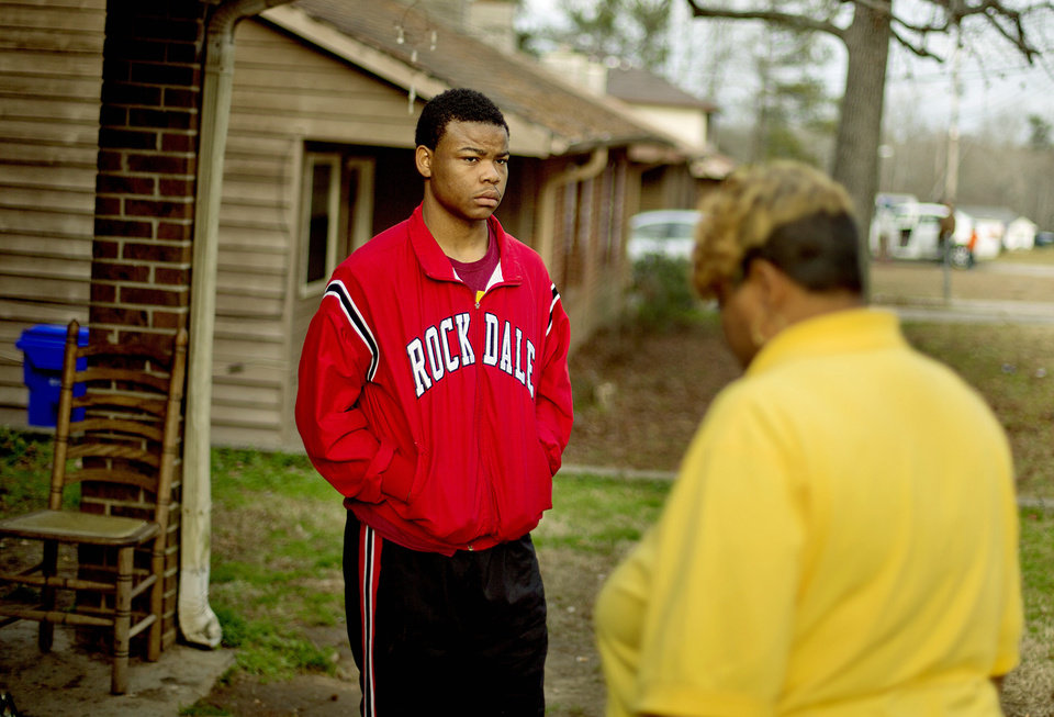 "Lamonta Stroud, 18, left, stands outside his home across the street from the scene of a house fire that killed four children, including an infant, Wednesday, Jan. 9, 2013, in Conyers, Ga. Stroud said he ran into the duplex, smashing windows and pleading with the children to come to a bathroom and escape. ""I just started hitting windows, breaking windows, screaming 'come to the bathroom, I can get you all out,'"" Stroud recalled. ""There really wasn't that much I could do. I tried."" (AP Photo/David Goldman)"