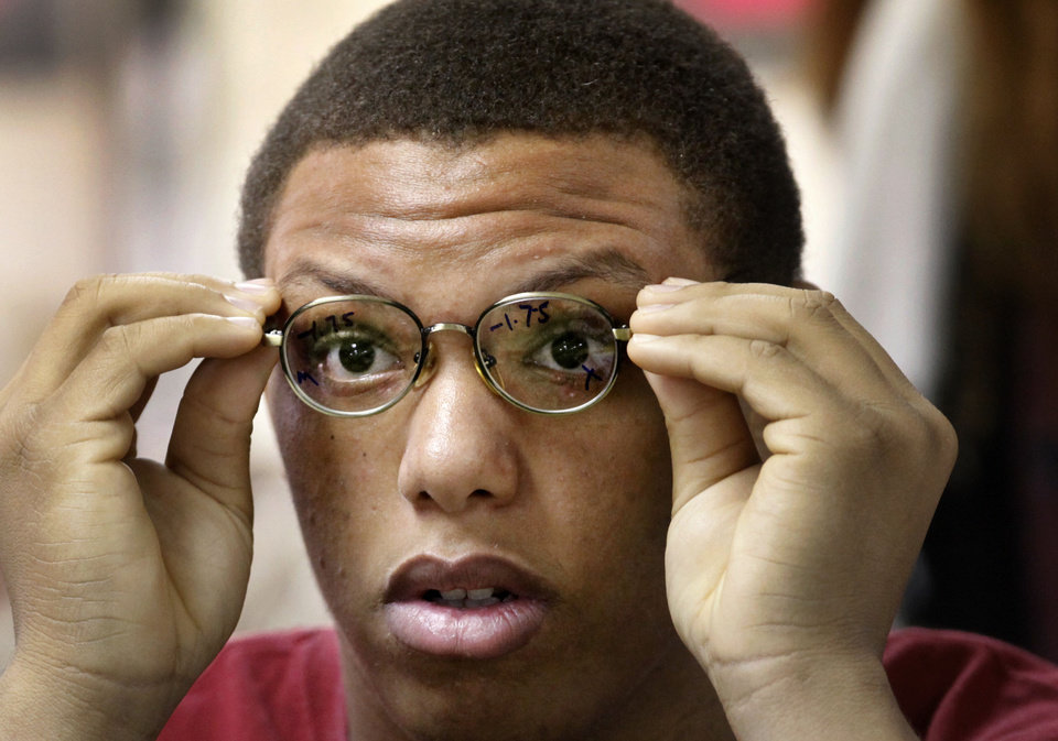 Photo - Marguess Smith, 17, of Oklahoma City, looks at an eye chart through his new glasses.