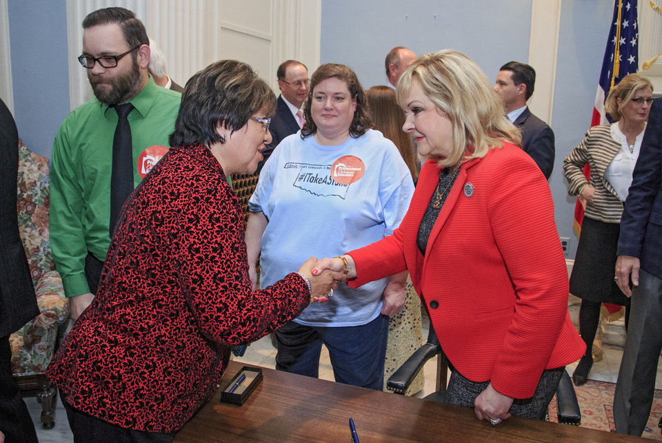 Photo -  Gov. Mary Fallin shakes hands with North Rock Creek School teacher Esther Bell after Fallin signed House Bill 1023xx at the Capitol on Thursday. North Rock Creek schools remained open Monday. [Photo by Chris Landsberger, The Oklahoman]