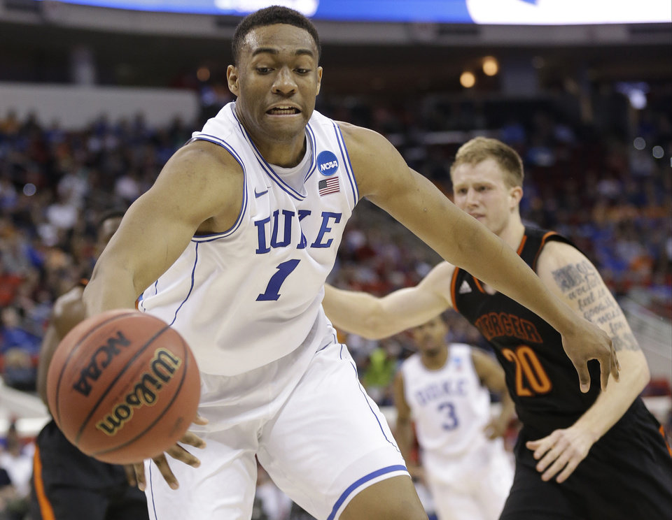 Photo - Duke forward Jabari Parker (1) works against Mercer forward Jakob Gollon (20) during the first half of an NCAA college basketball second-round game, Friday, March 21, 2014, in Raleigh, N.C. (AP Photo/Gerry Broome)