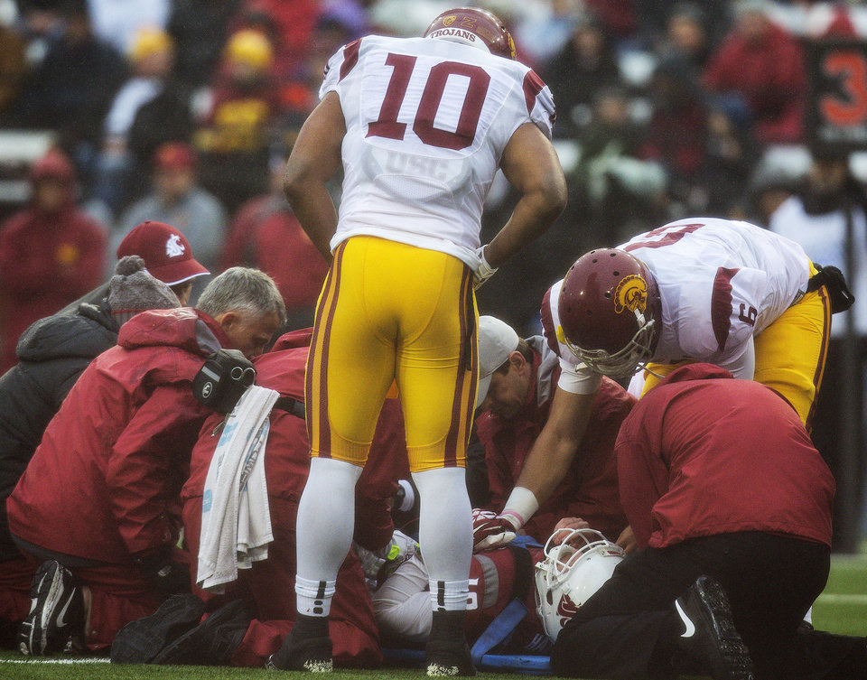 Photo - Southern California team captains linebacker Hayes Pullard (10) and quarterback Cody Kessler (6) check on injured Washington State quarterback Connor Halliday (12) during the first quarter of an NCAA college football game, Saturday, Nov. 1, 2014, at Martin Stadium in Pullman, Wash. Halliday was taken off the field and transported to at Pullman Regional Hospital in Pullman with a splint on his right leg. (AP Photo/Dean Hare)