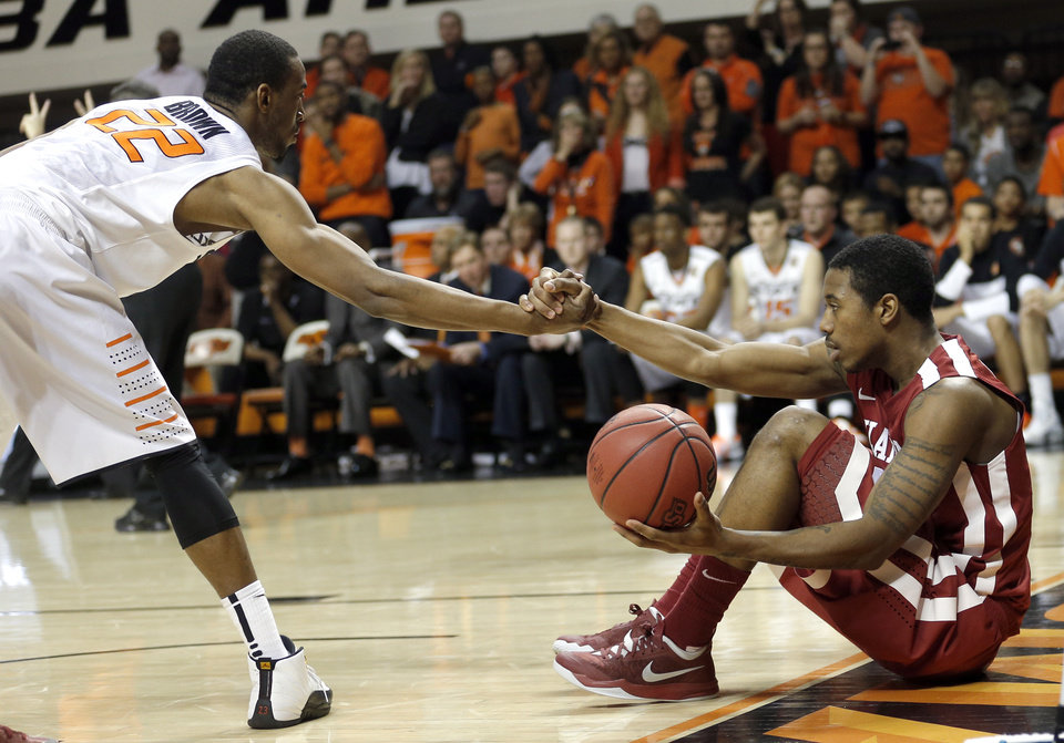 Photo - Oklahoma State's Markel Brown (22) helps up Oklahoma's Je'lon Hornbeak (5)  after fouling him during the men's Bedlam college game between Oklahoma and Oklahoma State at Gallagher-Iba Arena in Stillwater, Okla., Saturday, Feb. 15, 2014. Photo by Sarah Phipps, The Oklahoman