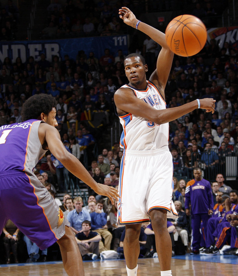 Photo - Oklahoma City's Kevin Durant (35) passes the ball away from Josh Childress (1) of Phoenix during the NBA basketball game between the Oklahoma City Thunder and Phoenix Suns at Chesapeake Energy Arena in Oklahoma City, Saturday, Dec. 31, 2011. Photo by Nate Billings, The Oklahoman