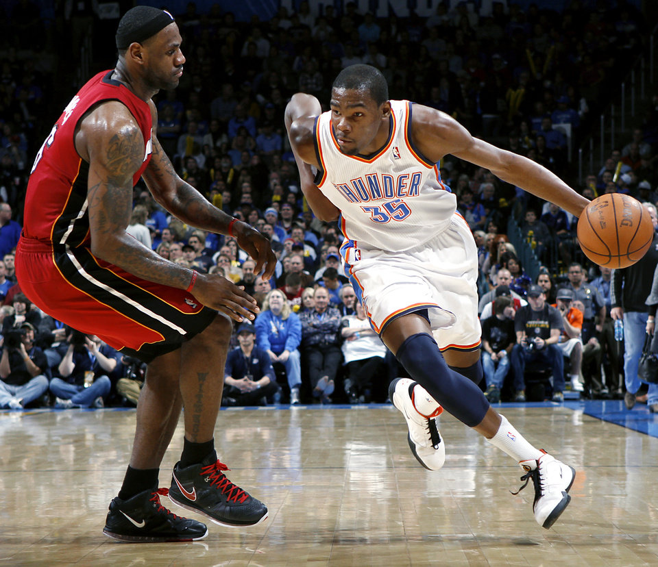 Photo - Oklahoma City's Kevin Durant dribbles around Miami's LeBron James during their NBA basketball game at the OKC Arena in Oklahoma City on Thursday, Jan. 30, 2011. The Heat beat the Thunder 108-103. Photo by John Clanton, The Oklahoman