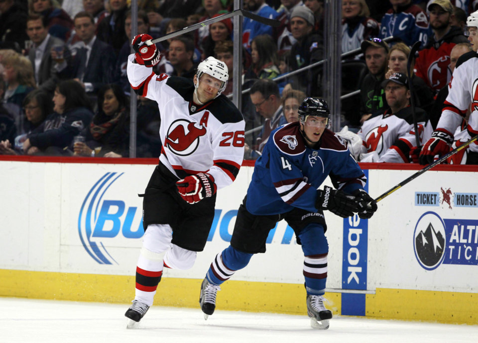 Photo - New Jersey Devils left wing Patrik Elias, left, of the Czech Republic, pursuea the puck with Colorado Avalanche defenseman Tyson Barrie in the first period of an NHL hockey game in Denver, Thursday, Jan. 16, 2014. (AP Photo/David Zalubowski)