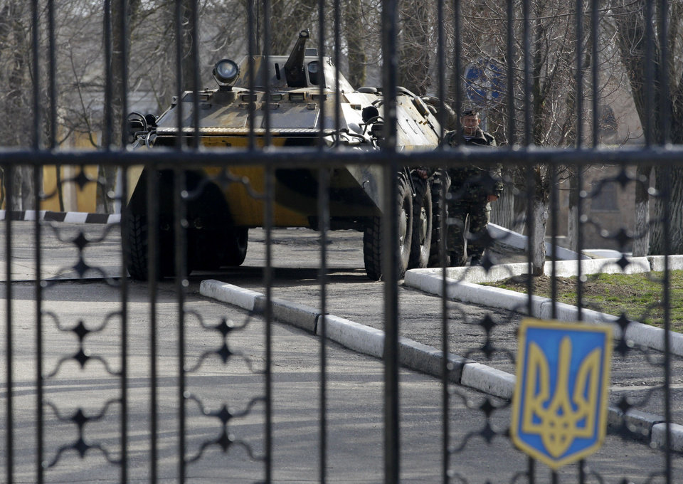 Photo - A Ukrainian armored personnel carrier is stationed behind the gate of a military base in the port of Kerch, Ukraine, Monday, March 3, 2014. Pro-Russian troops controlled a ferry terminal on the easternmost tip of Ukraine's Crimea region close to Russia on Monday, intensifying fears that Moscow will send even more troops into the strategic Black Sea region in its tense dispute with its Slavic neighbor. (AP Photo/Darko Vojinovic)