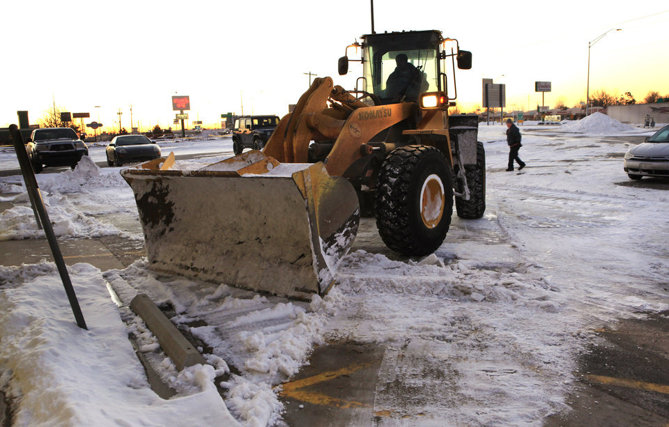 Photo - A loader works at sunrise to clear snow and ice from a shopping mall parking lot at I-240 and S Pennsylvania in Oklahoma City Thursday, Feb. 10, 2011. Photo by Paul B. Southerland, The Oklahoman