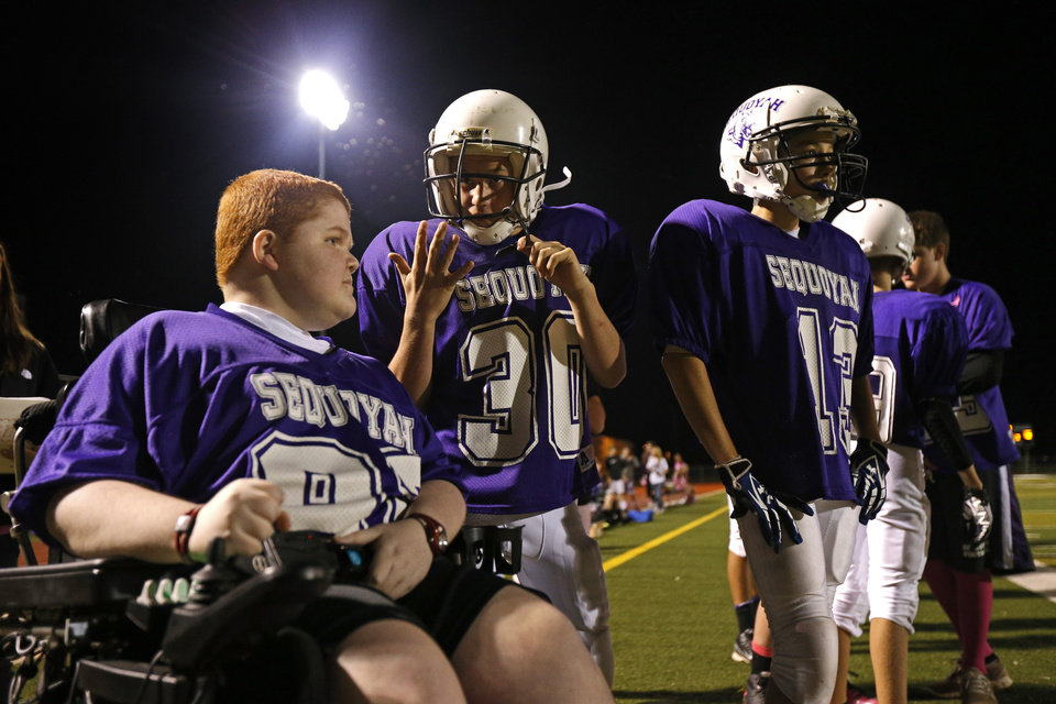 Keegan Erbst talks with Matt Ashcraft, center, and Lucas Coker during a Sequoyah Middle School football game, Thursday, September 27, 2012. Keegan, who has muscular dystrophy and is confined to a wheelchair, got involved with the team after players Lucas Coker, Colton James, and Parker Tumleson, pushed suggested it to the coach.  Photo by Bryan Terry, The Oklahoman