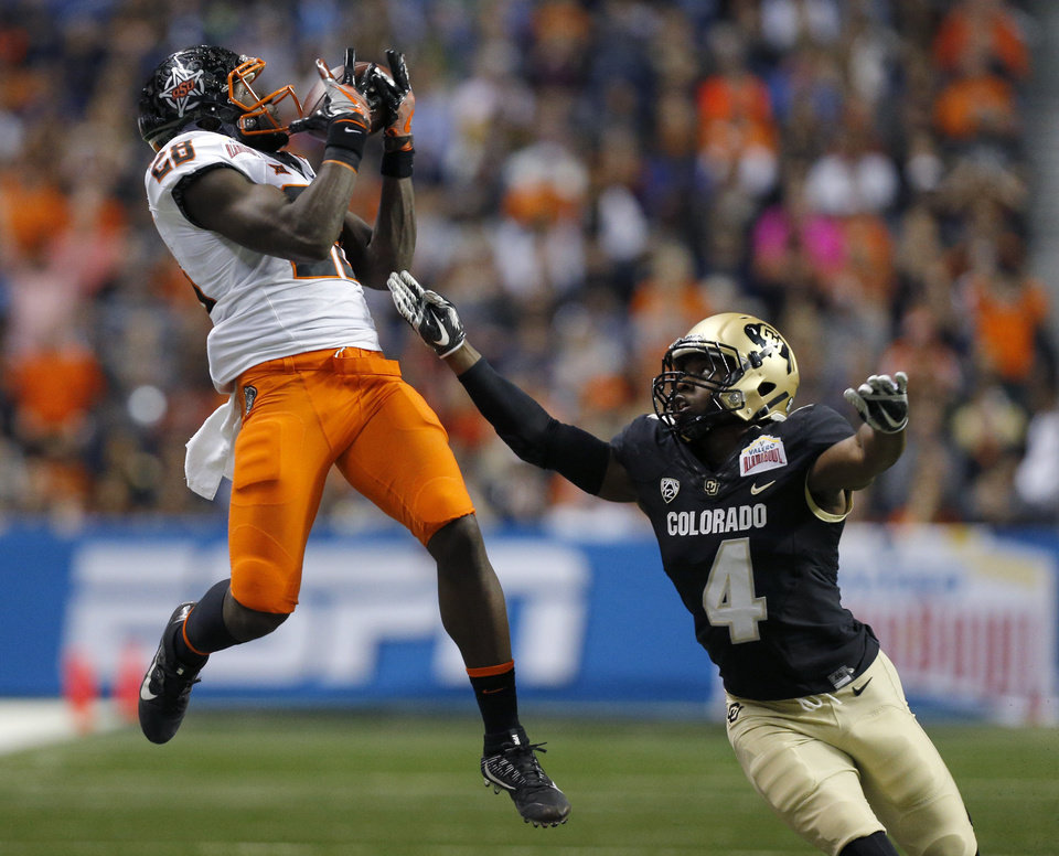 Photo - Oklahoma State's James Washington (28) makes a catch in front of Colorado's Chidobe Awuzie (4) in the second quarter during the Valero Alamo Bowl college football game between the Oklahoma State Cowboys and the Colorado Buffaloes at the Alamodome in San Antonio, Thursday, Dec. 29, 2016. Photo by Sarah Phipps, The Oklahoman
