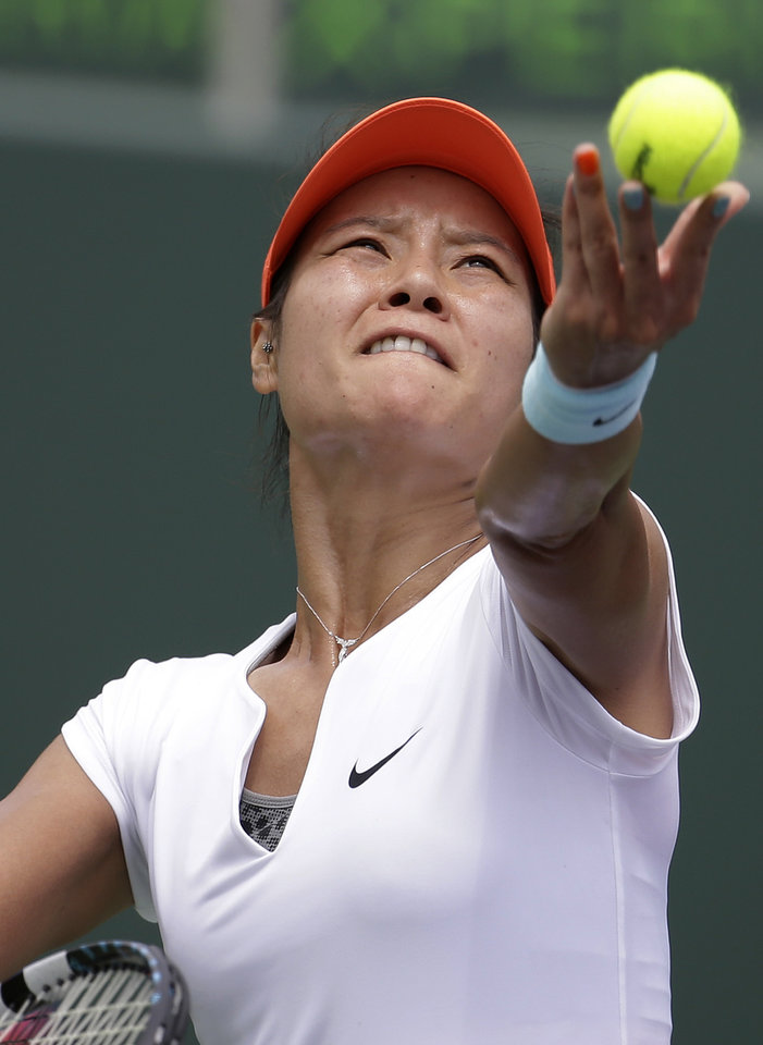 Photo - Li Na, of China, tosses the ball to serve to Serena Williams during the women's final at the Sony Open Tennis tournament, Saturday, March 29, 2014, in Key Biscayne, Fla. (AP Photo/Lynne Sladky)