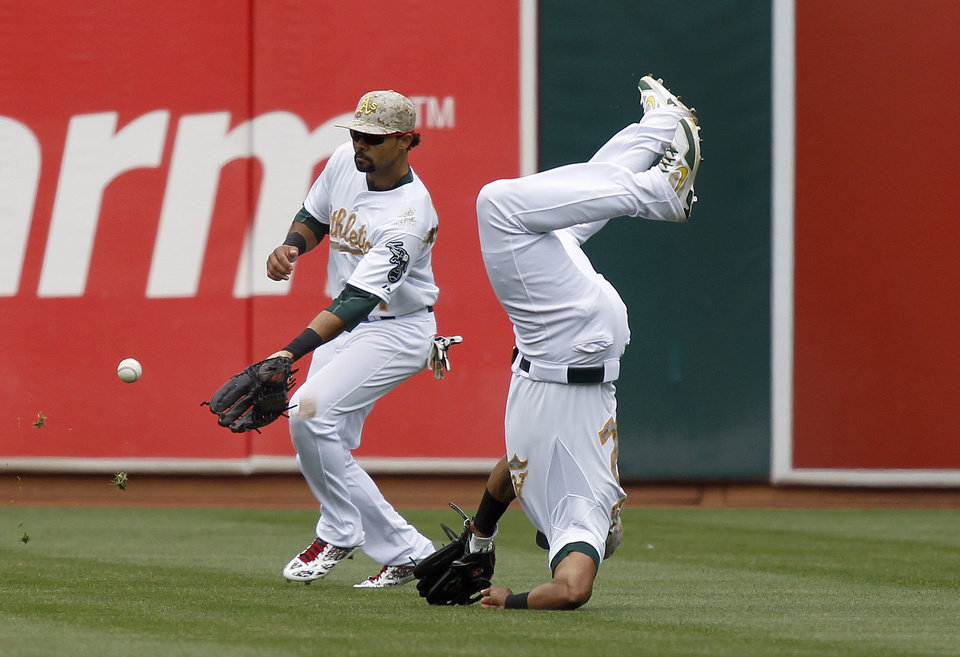 Photo - Oakland Athletics left fielder Yoenis Cespedes flips over after missing a shallow fly ball off the bat of San Francisco Giants' Brandon Crawford as center fielder Coco Crisp (4) backs him up during the fifth inning of a baseball game in Oakland, Calif., Monday, May 27, 2013. (AP Photo/Tony Avelar)