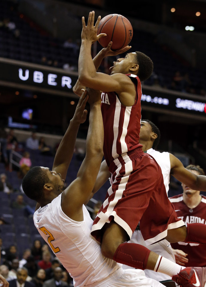 Photo - Oklahoma guard Isaiah Cousins, top, shoots as he is fouled by George Mason forward Johnny Williams (2) during the first half of an NCAA college basketball game in the BB&T Classic, Sunday, Dec. 8, 2013, in Washington. (AP Photo/Alex Brandon)