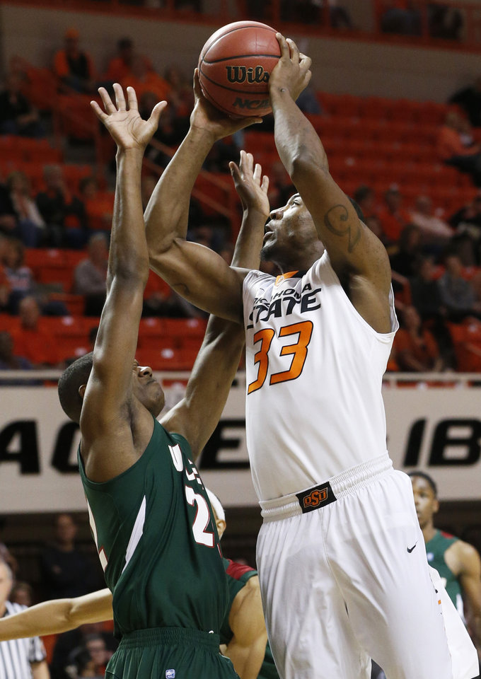 Photo - Oklahoma State guard Marcus Smart (33) shoots over Mississippi Valley State forward Blake Ralling (22) in the first half of an NCAA college basketball game in Stillwater, Okla., Friday, Nov. 8, 2013. (AP Photo/Sue Ogrocki)
