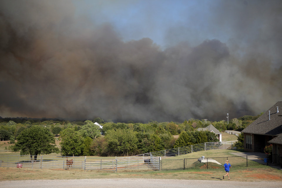 Photo - A resident runs towards her home as flames from a wildfire approach near NW 122nd and Midwest Blvd. in Oklahoma City, Wednesday, August 31, 2011. Photo by Bryan Terry, The Oklahoman