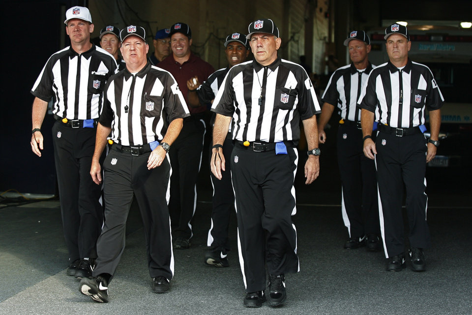 Photo -   FILE - In this Aug. 9, 2012, file photo, officials walk towards the field for an NFL football game between the Buffalo Bills and the Washington Redskins in Orchard Park, N.Y. The NFL and referees' union reached a tentative agreement on Wednesday, Sept. 26, to end a three-month lockout that triggered a wave of frustration and anger over replacement officials and threatened to disrupt the rest of the season. (AP Photo/Bill Wippert, File)