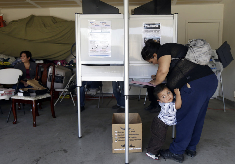 Photo -   Yesenia Perez marks her ballot as her 1-year-old Eduardo Sanchez clings to her in the Weston Ranch area of Stockton, Calif. on Tuesday, Nov. 6, 2012. The neighborhood was heavily affected by foreclosures in the past few years. Perez, 34, a mother of five who works at a local fruit-packing house, has had her share of hard times. After both she and her husband had their work hours cut amid the sputtering economy, they lost their home to foreclosure three years ago. Yet on Tuesday, she felt compelled to do something she had never done before: vote. (AP Photo/Marcio Jose Sanchez)