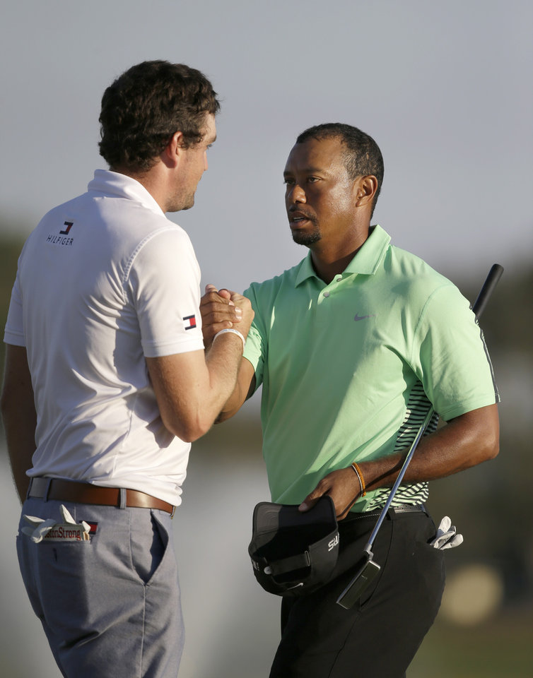 Photo - Tiger Woods, right, and Keegan Bradley congratulate each other after finishing the second round of the Honda Classic golf tournament, Friday, Feb. 28, 2014, in Palm Beach Gardens, Fla. (AP Photo/Wilfredo Lee)