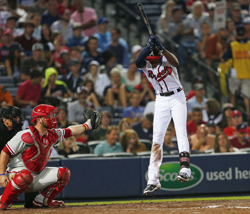 Photo - Atlanta Braves' B.J. Upton avoids being hit with a pitch as Philadelphia Phillies catcher Cameron Rupp makes the catch in the fourth inning of a baseball game in Atlanta, Friday, July 18, 2014. (AP Photo/John Bazemore)