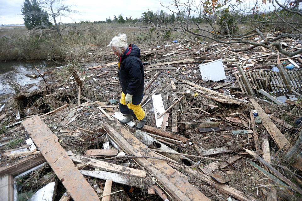 Tricia Burke walks over debris which washed up onto her property in the wake of superstorm Sandy, Thursday, Nov. 1, 2012, in Brick, N.J. Three days after Sandy slammed the mid-Atlantic and the Northeast, New York and New Jersey struggled to get back on their feet, the U.S. death toll climbed to more than 80, and more than 4.6 million homes and businesses were still without power. (AP Photo/Julio Cortez) ORG XMIT: NJJC115