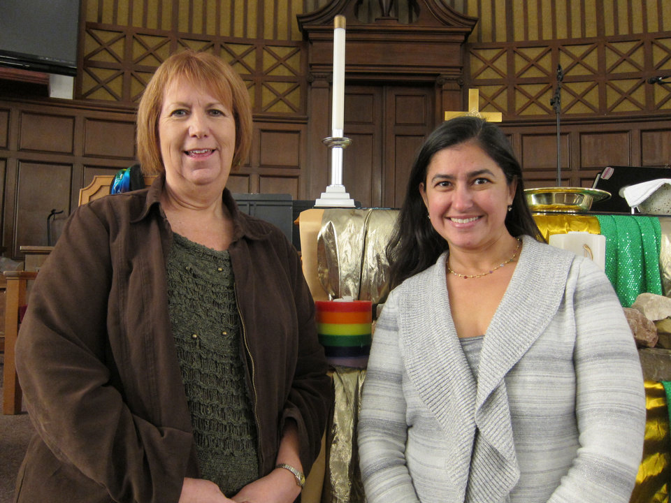 The Rev. Deborah Ingraham and the Rev. Trina Bose North, both of Edmond, stand next to the rainbow candle at Epworth United Methodist Church, where Ingraham is senior pastor. <strong>Carla Hinton - The Oklahoman</strong>