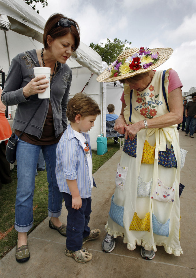 Photo - Teresa Whynne watches as son Parker, 4, picks a toy from the pockets of Joan Steed, Miss Pick Pocket, during May Fair Arts Festival in Norman, Okla. on Friday, May 1, 2009.   Photo by Steve Sisney, The Oklahoman