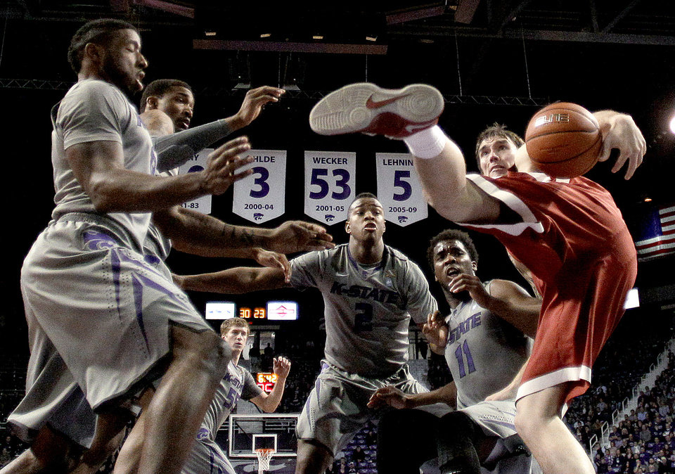 Oklahoma's Ryan Spangler, right, chases a loose ball with Kansas State's Omari Lawrence, Shane Southwell, Marcus Foster and Nino Williams (11), from left, during the first half of an NCAA college basketball game Tuesday, Jan. 14, 2014, in Manhattan, Kan. (AP Photo/Charlie Riedel)