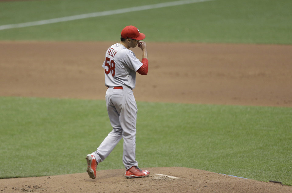 Photo - St. Louis starting pitcher Joe Kelly walks back to the mound against the Milwaukee Brewers during the first inning of a baseball game Friday, July 11, 2014, in Milwaukee. (AP Photo/Jeffrey Phelps)
