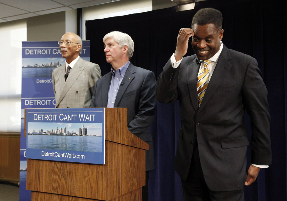 Photo - Kevyn Orr, right, reacts to a question as Detroit Mayor Dave Bing, left, and Gov. Rick Snyder, center, listen during a news conference in Detroit, Thursday, March 14, 2013. Snyder announced that he had chosen Orr, a partner in the Cleveland-based law and restructuring Jones Day firm, as Detroit's emergency manager. Snyder's already declared a financial emergency in Detroit, saying local officials lacked a plan to solve it. (AP Photo/Paul Sancya)