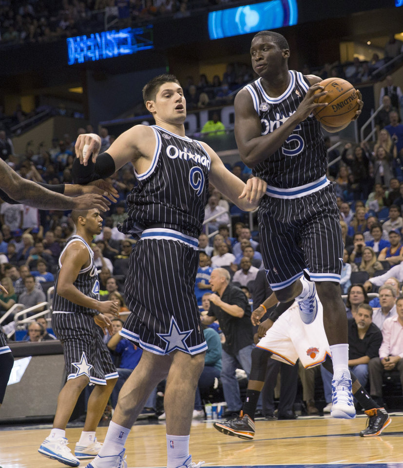 Photo - Orlando Magic's Victor Oladipo (5) rebounds the ball as Nikola Vucevic (9) watches during overtime of an NBA basketball game against the New York Knicks in Orlando, Fla., Friday, Feb. 21, 2014. The Magic won 129-121 in two overtimes. (AP Photo/Willie J. Allen Jr.)