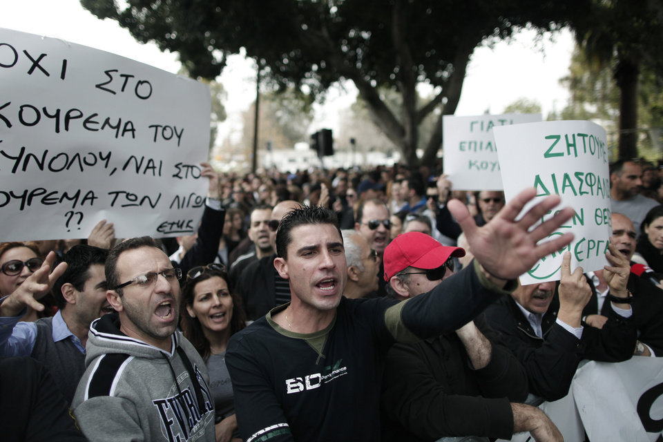"Protesting employees of Laiki bank chant slogans outside the Cypriot parliament, Friday, March 22, 2013. Cypriot authorities were putting the final touches Friday to a plan they hope will convince international lenders to provide the money the country urgently needs to avoid bankruptcy within days. ""The next few hours will determine the future of this country,"" said government spokesman Christos Stylianides.(AP Photo/Petros Giannakouris)"