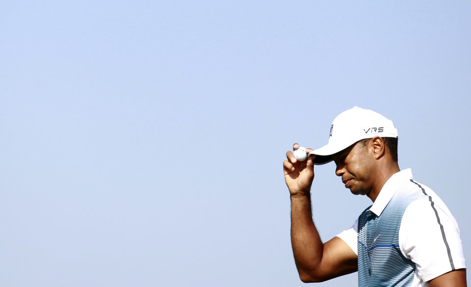Photo - Tiger Woods of the US touches his hat as he walks off the 1st green during the first day of the British Open Golf championship at the Royal Liverpool golf club, Hoylake, England, Thursday July 17, 2014. (AP Photo/Peter Morrison)