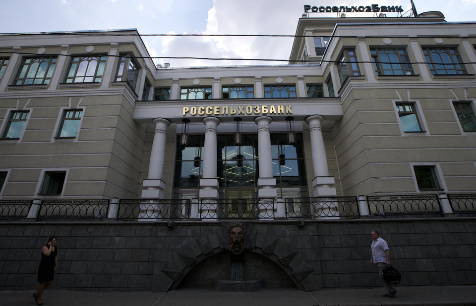 Photo - People walk past the headquarters of Russian Agricultural Bank in downtown Moscow, Russia, on Wednesday, July 30, 2014. The European Union approved dramatically tougher economic sanctions Tuesday, July 29, against Russia, followed swiftly by a new round of U.S. penalties. Among the targets were three Russian banks: the Bank of Moscow, Russian Agricultural Bank and VTB Bank, Russia's second largest bank. (AP Photo/Ivan Sekretarev)