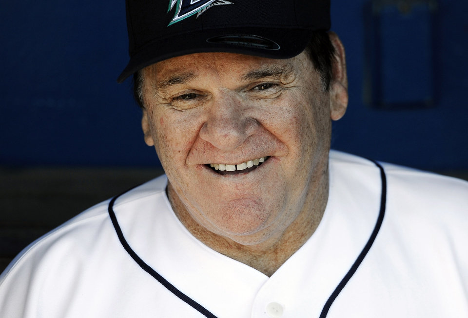 Photo - FILE - In this June 16, 2014, file photo, Pete Rose sits in the dugout at The Ballpark at Harbor Yard in Bridgeport, Conn. Rose may have a role to play in next year's All-Star game in Cincinnati despite his lifetime ban from baseball. The career hits leader generally is not allowed in any areas of major league ballparks not open to fans. (AP Photo/Jessica Hill, File)