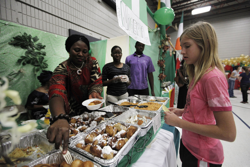 Photo - Rita Offiah, of Oklahoma City, serves Nigerian food to Emma Barrett, 12, of Oklahoma City, during a multicultural food festival at St. Eugene Catholic Church in Oklahoma City, Sunday, Sept. 9, 2012.  Photo by Garett Fisbeck, The Oklahoman  Garett Fisbeck - Garett Fisbeck