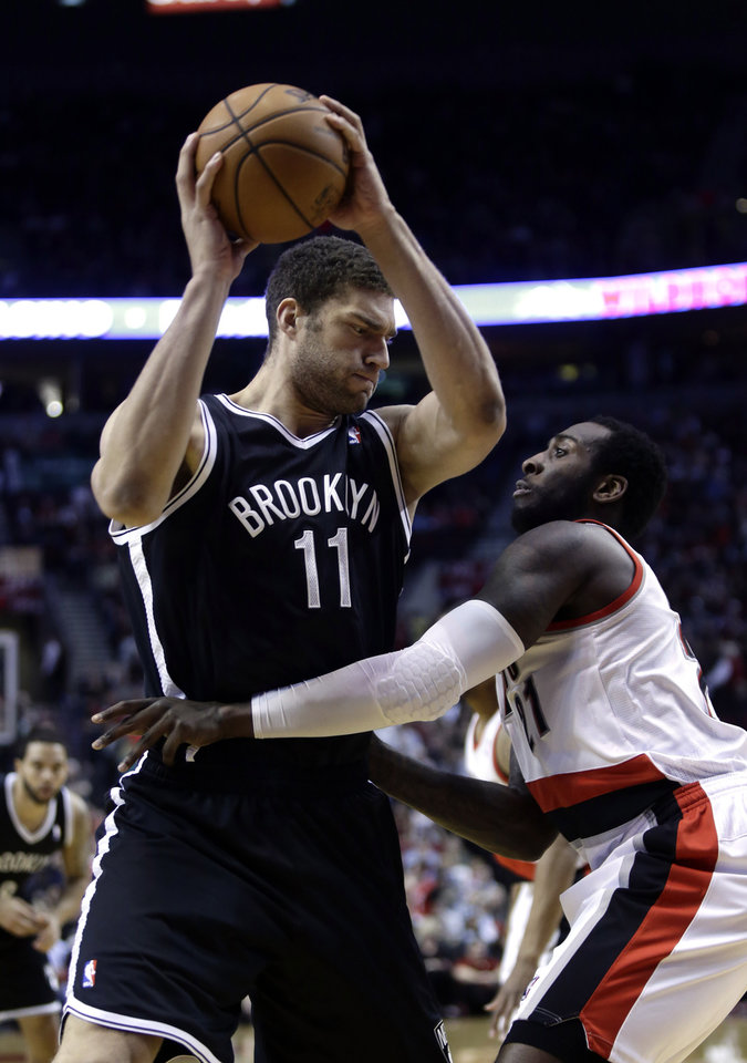 Photo - Brooklyn Nets center Brook Lopez, left, works the ball against Portland Trail Blazers center J.J. Hickson during the first quarter of an NBA basketball game in Portland, Ore., Wednesday, March 27, 2013.(AP Photo/Don Ryan)