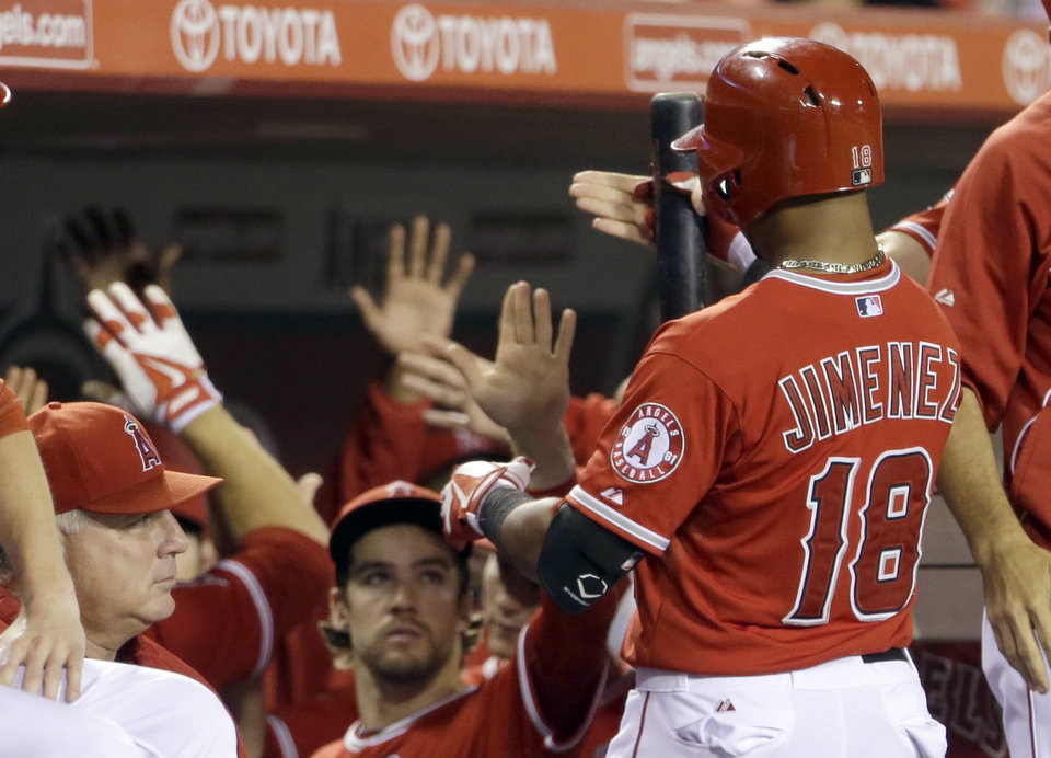 Photo - Los Angeles Angels teammates greet Luis Jimenez after his sacrifice fly scored a run against the Tampa Bay Rays in the sixth inning of a baseball game in Anaheim, Calif., Monday, Sept. 2, 2013. (AP Photo/Reed Saxon)