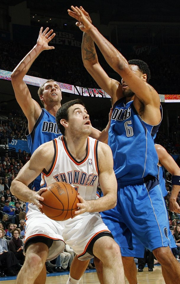 Oklahoma City's Nick Collison (4) tries to get the ball past the defense of Dirk Nowitzki (41) and Tyson Chandler (6) of Dallas during the NBA basketball game between the Dallas Mavericks and the Oklahoma City Thunder at the Oklahoma City Arena in Oklahoma City, Monday, Dec. 27, 2010. Photo by Nate Billings, The Oklahoman