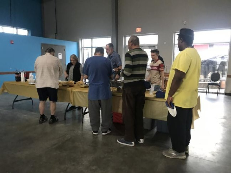 Photo -  Residents of the Oklahoma City Homeless Alliance's WestTown load up on snacks during the Super Soul Party hosted at the homeless alliance's day shelter on Feb. 2 by Chabad Community Center for Jewish Life and Learning. [Carla Hinton/The Oklahoman]