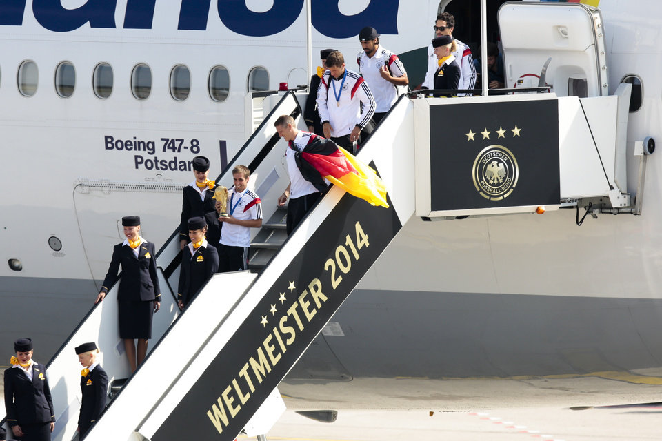 """Photo - The players of German national soccer team Philipp Lahm, Sebastian Schweinsteiger, Thomas Mueller, Sami Khedira and Mats Hummels from left,  arrive at Tegel  airport  in Berlin Tuesday, July 15, 2014.  G Germany's World Cup-winning team has returned home  from Brazil to celebrate the country's fourth title with huge crowds of fans. The team's Boeing 747 touched down at Berlin's Tegel airport midmorning Tuesday after flying a lap of honor over the """"fan mile"""" in front of the landmark Brandenburg Gate. Words read World Champion 2014.  (AP Photo/Markus Schreiber)"""