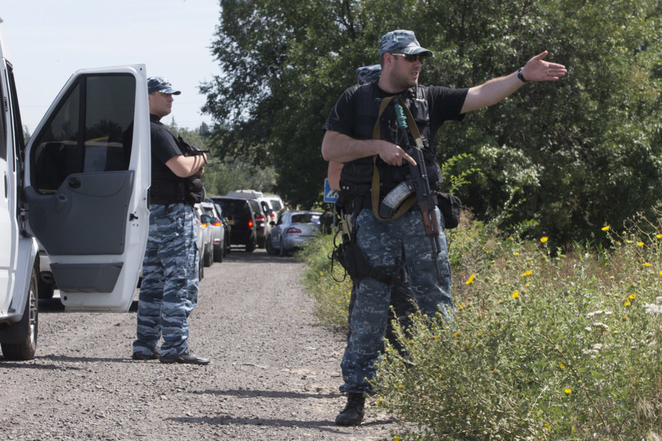 Photo - Self-proclamed Donetsk People's Republic policemen guard a convoy of International forensic experts, Dutch and Australian policemen and members of the OSCE mission in Ukraine approach Shakhtarsk, Donetsk region, eastern Ukraine on Monday, July 28, 2014. An international police team abandoned its attempt to reach the crash site of a Malaysia Airlines plane for a second day running Monday as clashes raged in a town on the road to the area.(AP Photo/Dmitry Lovetsky)
