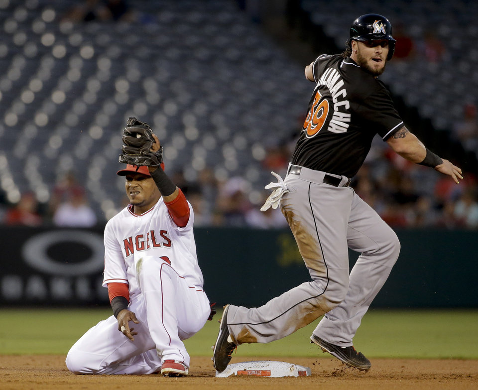 Photo - Miami Marlins' Jarrod Saltalamacchia, right, reacts after being tagged out by Los Angeles Angels shortstop Erick Aybar on a ground-out to first by Adeiny Hechavarria during the second inning of a baseball game in Anaheim, Calif., Monday, Aug. 25, 2014. (AP Photo/Chris Carlson)