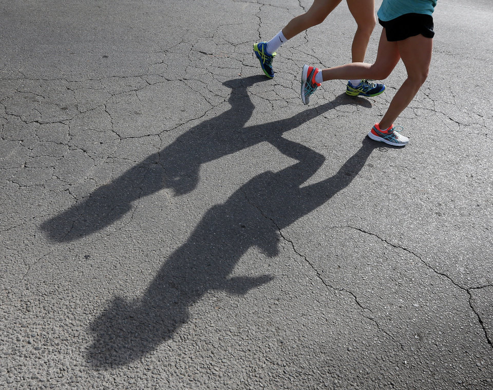 Photo - Runners cast shadows as they travel through Nichols Hills on Grand Blvd. during the Oklahoma City Memorial Marathon, Sunday, April 24, 2016. Photo by Nate Billings, The Oklahoman