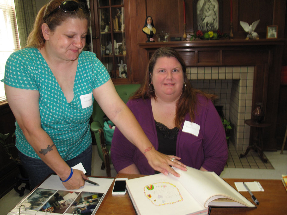 Photo - Jenni Touhey-McCreery and Becky Roberson look through Villa Teresa   School memory albums during a recent Carmelite Sisters of St. Therese alumni and 95th anniversary gathering at the Villa Teresa Convent and School in Oklahoma City. Photo by Carla Hinton  Carla Hinton - The Oklahoman