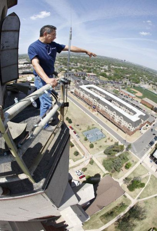 Photo - Facilities worker Victor Zuniga points out various landmarks from the catwalk at the top of the 286 ft. tall GoldStar Memorial building on the campus of Oklahoma City University in Oklahoma City, OK, Thursday, April 14, 2011. By Paul Hellstern, The Oklahoman ORG XMIT: KOD  PAUL HELLSTERN