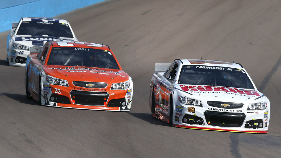 Photo - Dale Earnhardt, Jr., right, Brian Scott (33) and Jimmie Johnson (48) head into Turn 1 during the NASCAR Sprint Cup Series auto race Sunday, March 2, 2014, in Avondale, Ariz. (AP Photo/Ross D. Franklin)