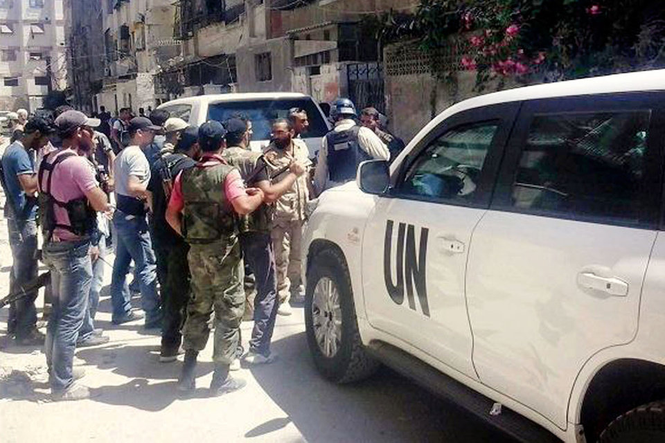Photo - In this citizen journalism image provided by the United media office of Arbeen which has been authenticated based on its contents and other AP reporting, Syrian rebels escorted the UN investigation team, in Damascus countryside of Zamalka, Syria, Wednesday, Aug. 28, 2013. U.N. chemical weapons experts headed to a Damascus suburb on Wednesday for a new tour of areas struck by a purported poison gas attack, activists said, as Western powers laid the groundwork for a possible punitive strike and the U.N. chief pleaded for more time for diplomacy. (AP Photo/United media office of Arbeen)
