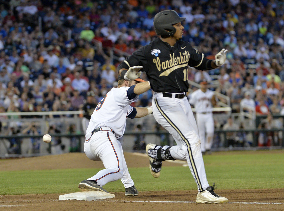 Photo - Vanderbilt's John Norwood (10) arrives at first with a single as Virginia first baseman Mike Papi (38) misses the throw during the sixth inning of Game 3 of the best-of-three NCAA baseball College World Series finals in Omaha, Neb., Wednesday, June 25, 2014. Norwood advanced to second. (AP Photo/Ted Kirk)