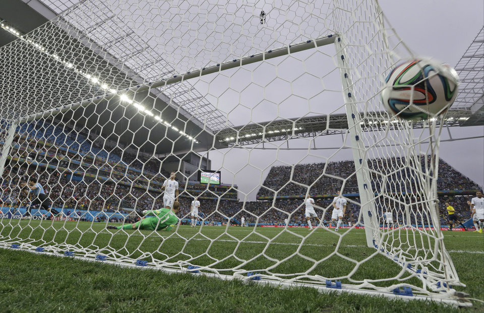 Photo - Uruguay's Luis Suarez, left, celebrates scoring the opening goal past England's goalkeeper Joe Hart during the group D World Cup soccer match between Uruguay and England at the Itaquerao Stadium in Sao Paulo, Brazil, Thursday, June 19, 2014.  (AP Photo/Felipe Dana)